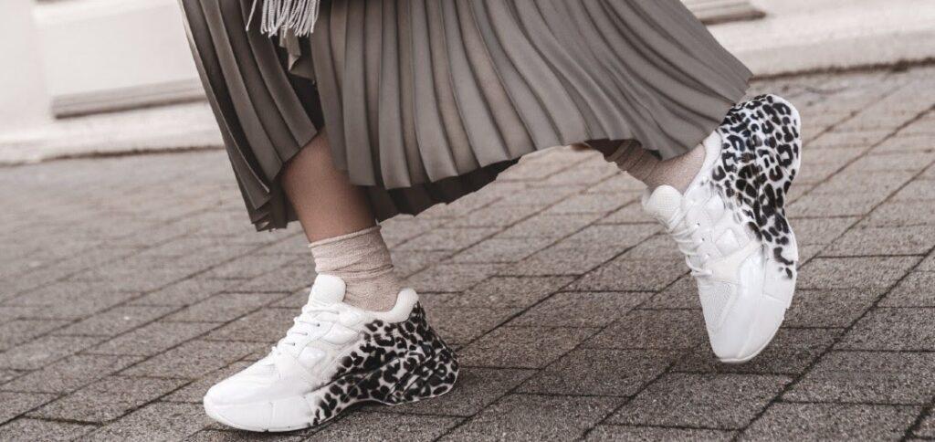 mujer con vestido largo y zapatillas blancas
