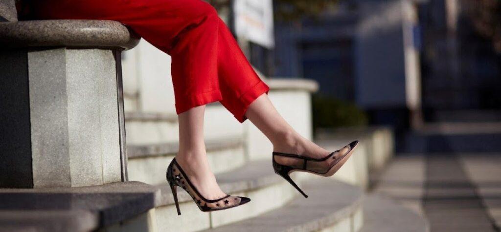 mujer en pantalón rojo y tacones de aguja